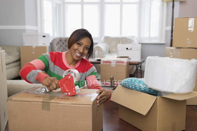 Verticale souriant, femme heureuse tapant la boîte en carton, maison mobile — Photo de stock