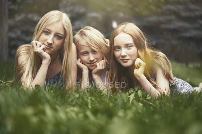 Портрет красивых сестер, лежащих в траве — стоковое фото