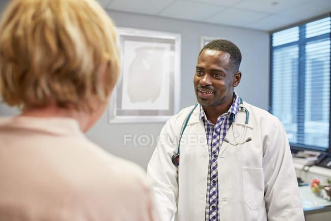 Medico di sesso maschile che parla con paziente anziana di sesso femminile in ufficio medici — Foto stock