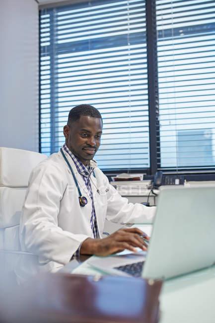 Врач-мужчина работает за ноутбуком в офисе врача — стоковое фото