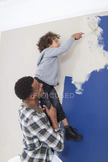 Padre e hijo pintando pared - foto de stock