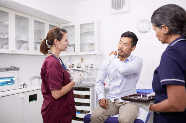 Paziente di sesso maschile che spiega il dolore alla spalla al medico di sesso femminile nella sala d'esame clinica — Foto stock