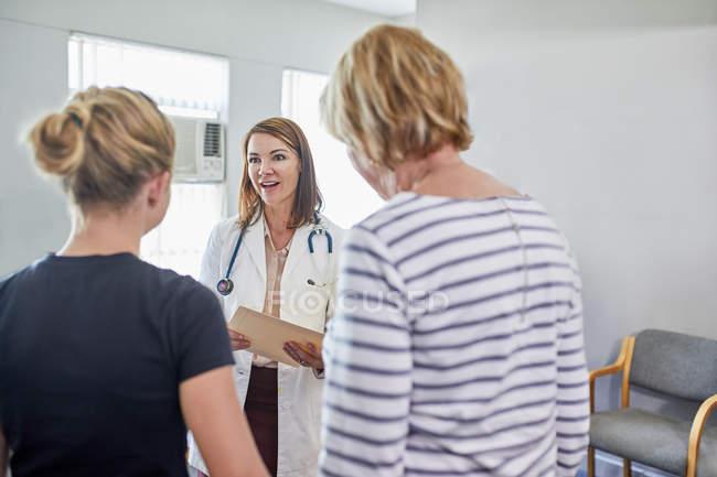 Pédiatre femme parlant avec une patiente en salle d'examen clinique — Photo de stock