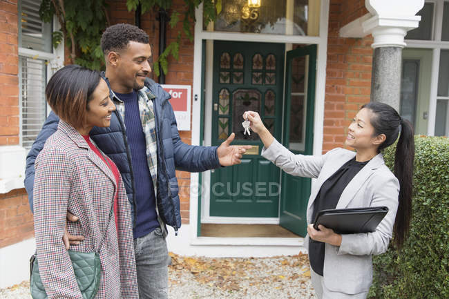 Real estate agent giving house keys to couple outside new house — Stock Photo