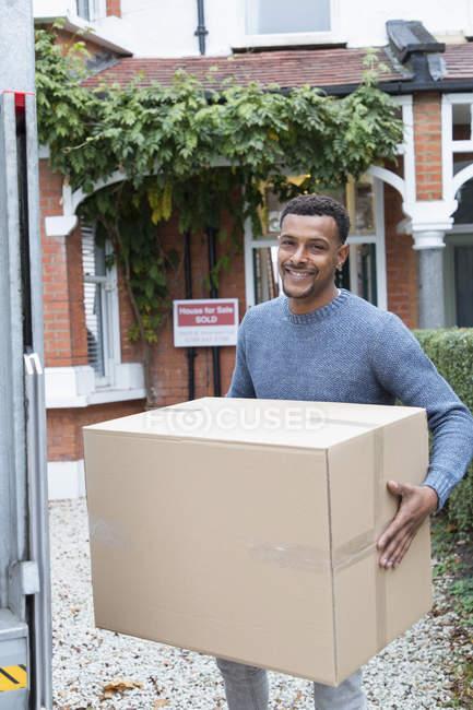 Retrato hombre confiado mudanza casa, llevando caja de cartón - foto de stock