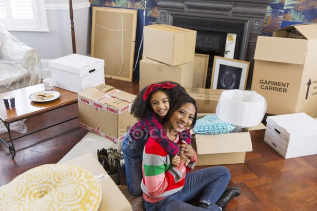 Ritratto felice, affettuosa madre e figlia che si abbracciano tra le scatole, casa mobile — Foto stock