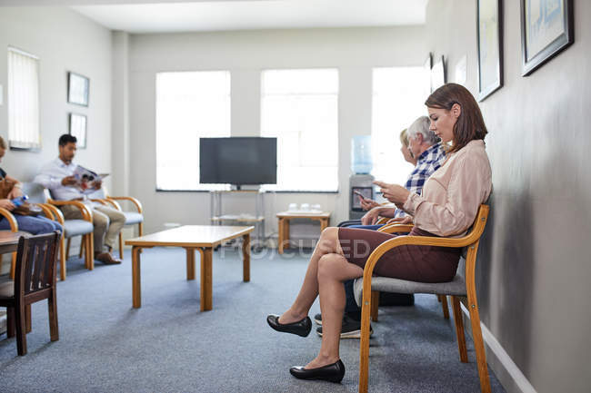 Woman using smart phone, waiting in clinic waiting room — Stock Photo
