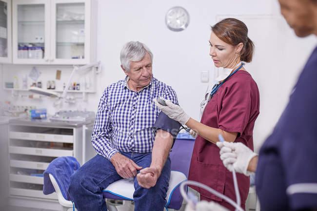 Medico che controlla la pressione sanguigna del paziente anziano nella sala visite della clinica — Foto stock
