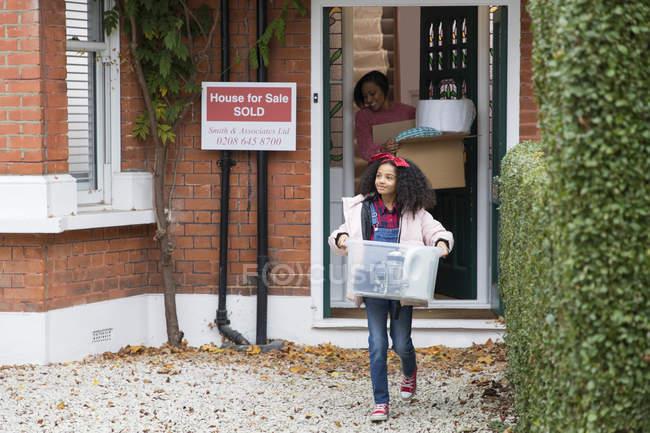 Chica mudándose fuera de casa, llevando pertenencias en la entrada - foto de stock