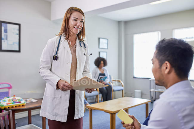 Female doctor talking with male patient in clinic waiting room — Stock Photo