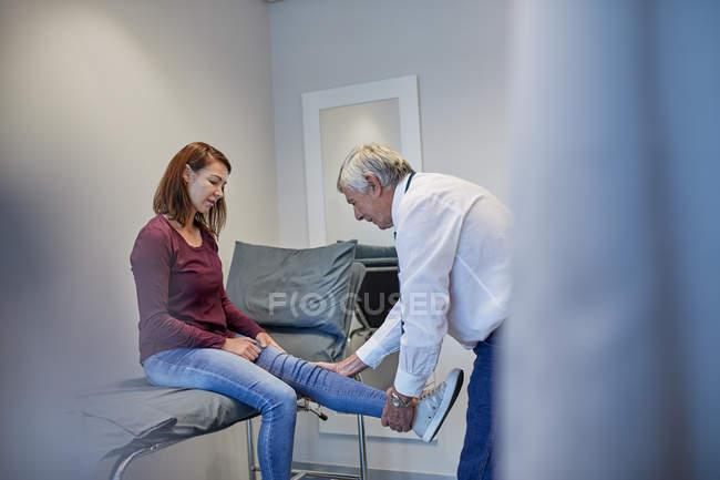 Male doctor examining woman leg in clinic examination room — Stock Photo