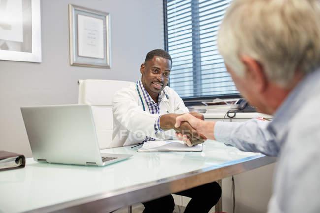 Médico masculino apertando as mãos com paciente sênior em consultório médico — Fotografia de Stock