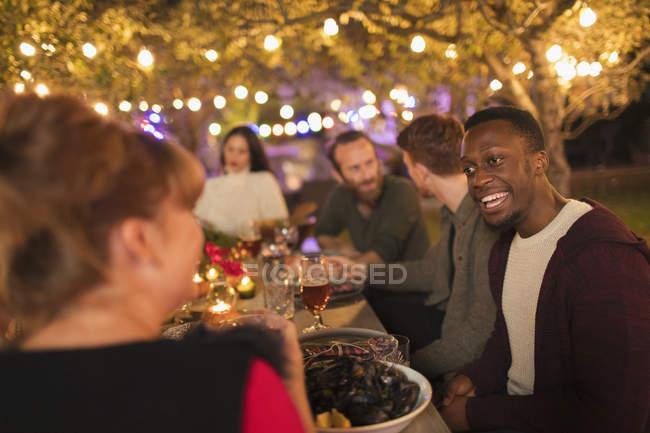 Friends talking, enjoying dinner garden party — Stock Photo