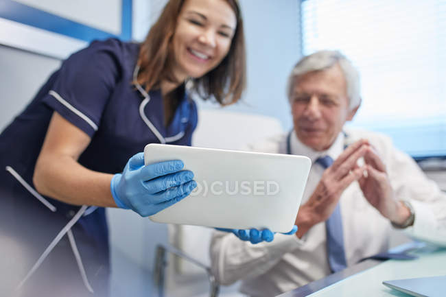 Doctor and nurse using digital tablet in clinic doctors office — Foto stock
