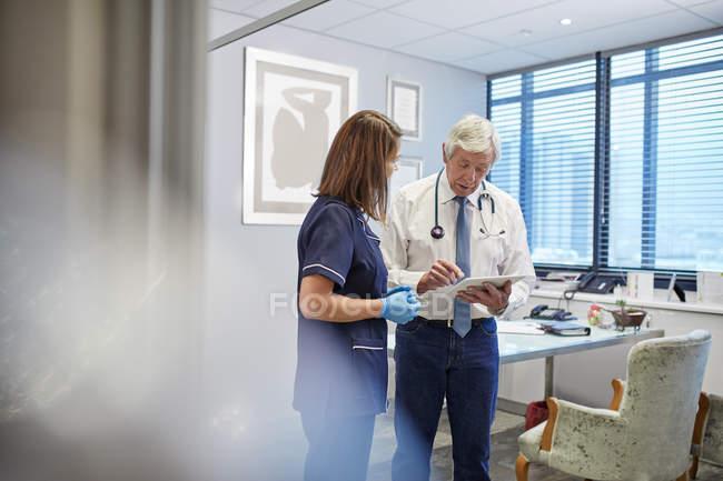 Médecin et infirmière avec tablette numérique parler, consultation dans le bureau des médecins de la clinique — Photo de stock
