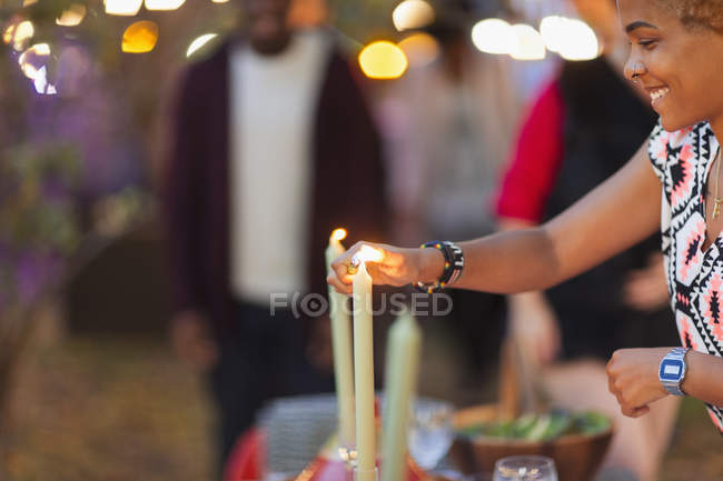 Жінка запалює свічки для обідньої вечірки. — стокове фото