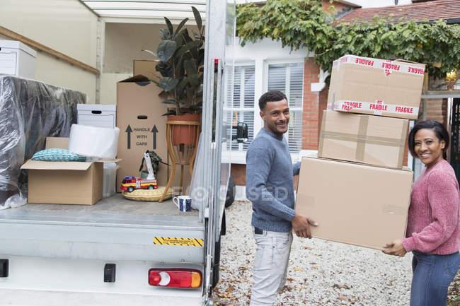 Retrato feliz pareja moviendo casa, descargando cajas de cartón de la furgoneta en movimiento - foto de stock