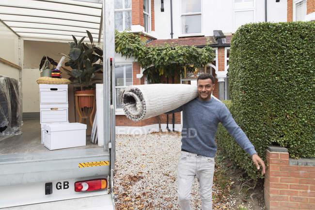 Retrato confiado hombre llevando alfombra fuera van en movimiento, casa en movimiento - foto de stock