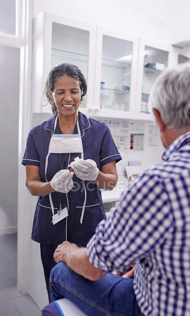 Female doctor taking blood from senior male patient in clinic examination room — Stock Photo