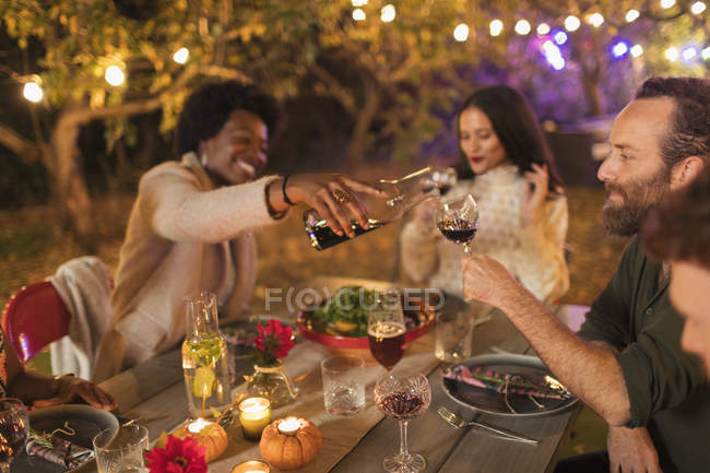 Friends pouring and drinking wine, enjoying dinner garden party — Stock Photo