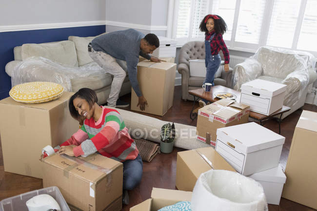 Family packing moving boxes, moving house — Stock Photo