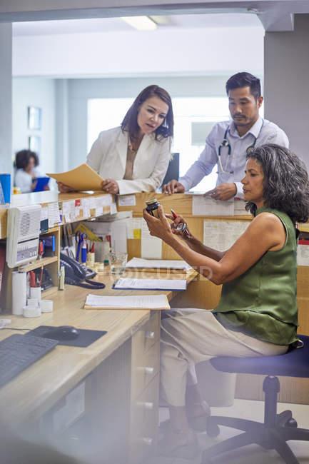 Médecins et réceptionniste examinant les médicaments à la réception de la clinique — Photo de stock