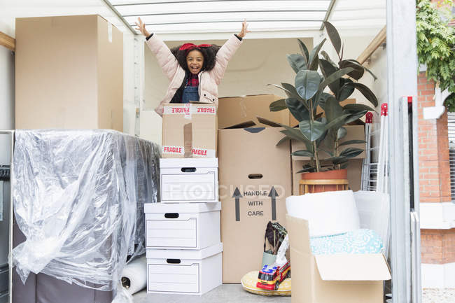 Portrait playful girl jumping up from behind cardboard boxes in moving van — Stock Photo