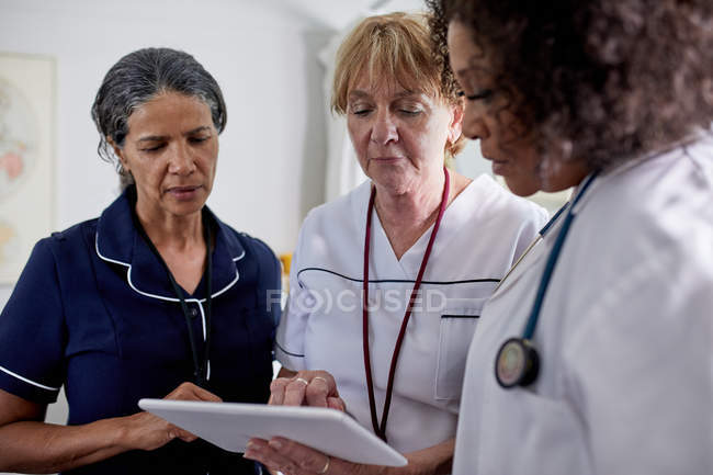 Doctora y enfermeras que usan tabletas digitales en la clínica - foto de stock