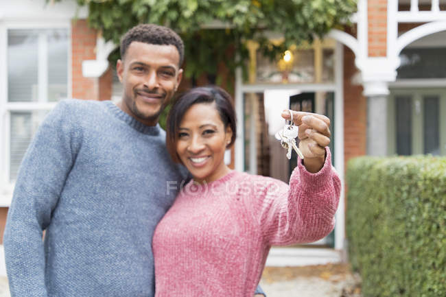 Portrait happy couple with house keys outside new house — Stock Photo
