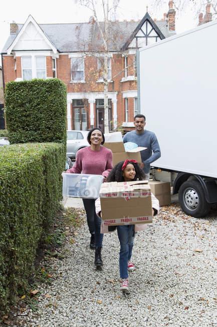 La familia se muda a una casa nueva, llevando pertenencias de la furgoneta en la entrada - foto de stock