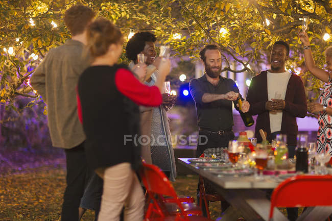 Friends celebrating, opening champagne at dinner garden party — Stock Photo