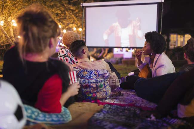 Friends watching movie on projection screen in backyard — Photo de stock