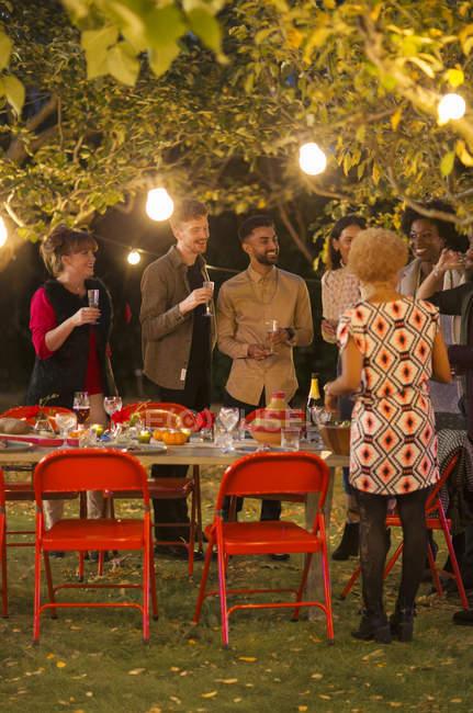 Amigos hablando bajo los árboles en la cena fiesta del jardín - foto de stock