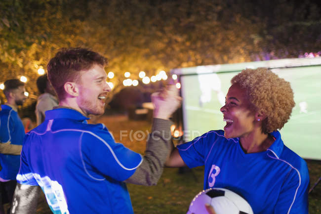 Happy friends cheering, watching soccer match on projection screen in backyard — Stock Photo