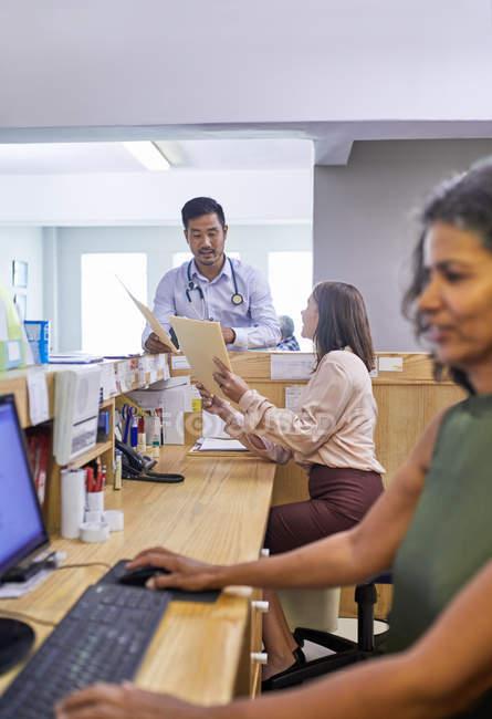 Médecin et réceptionniste avec dossiers médicaux parlant à la clinique — Photo de stock
