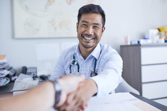 Ponto de vista médico feliz apertando as mãos com o paciente — Fotografia de Stock