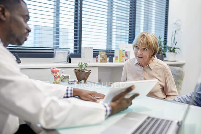 Médecin avec tablette numérique parlant au patient âgé dans le bureau des médecins — Photo de stock