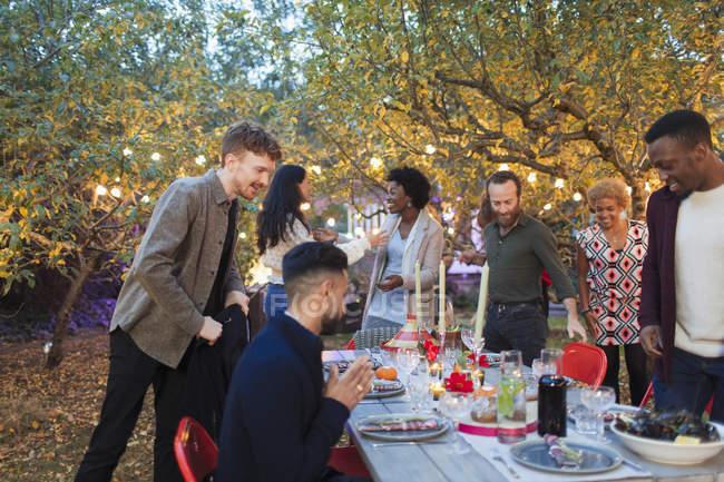 Arrivano gli amici, seduti per la cena festa in giardino — Foto stock
