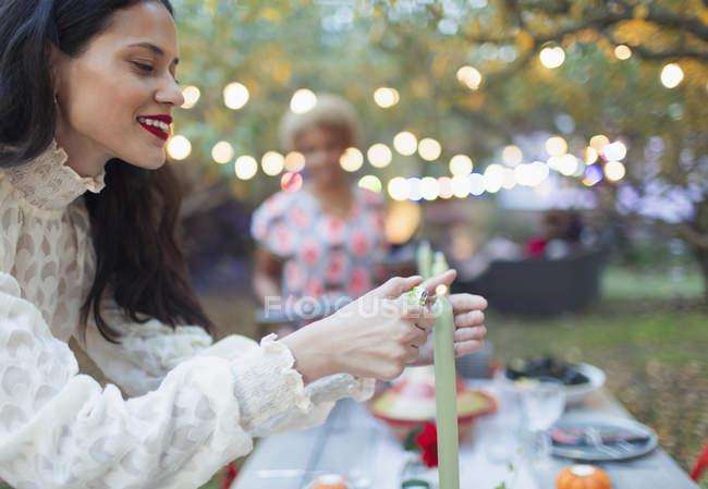 Mujer encendiendo velas para la cena fiesta en el jardín - foto de stock