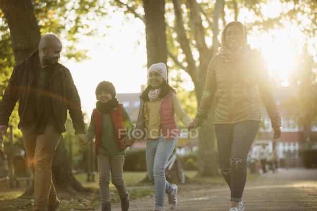Счастливая семья, держась за руки, гуляя в солнечном осеннем парке — стоковое фото