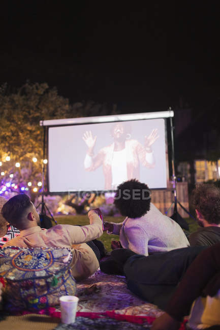 Friends watching movie on projection screen in backyard — Stock Photo