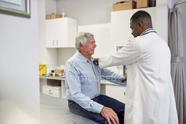 Врач-мужчина осматривает старшего пациента в комнате для обследования клиники — стоковое фото