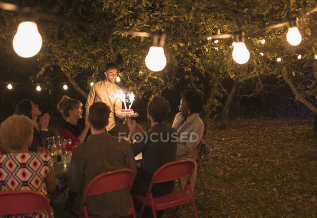 Amigos desfrutando de festa de aniversário com bolo sparkler no quintal com luzes de fadas — Fotografia de Stock