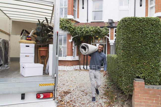 Retrato sonriente hombre llevando alfombra, saliendo de casa - foto de stock