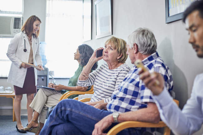 Medico e pazienti in sala d'attesa clinica — Foto stock