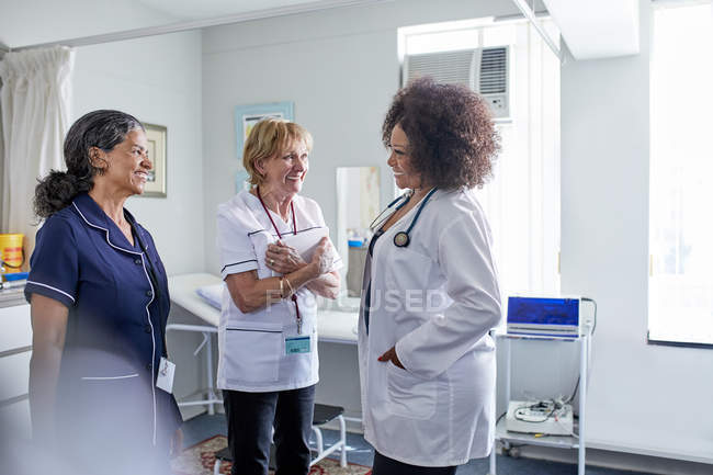 Female doctor and nurses talking in clinic examination room — Stock Photo