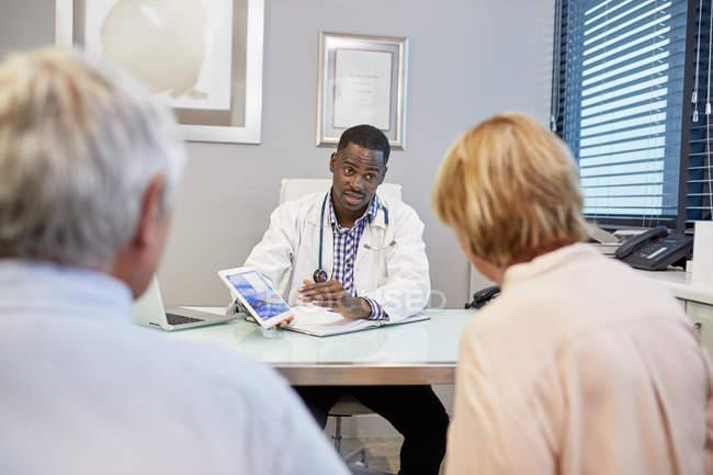 Medico con tablet digitale che parla con la coppia anziana nello studio medico della clinica — Foto stock