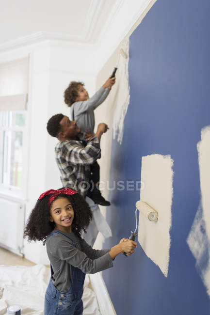 Portrait cute girl painting wall with father and brother — Stock Photo