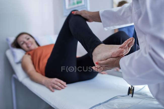 Médico examinando pierna de paciente femenina en sala de examen - foto de stock