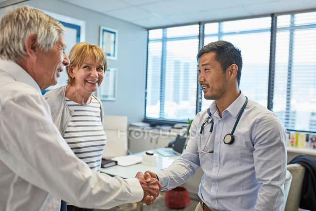Maschio medico stringendo la mano con gli anziani coppia in ambulatorio medici ufficio — Foto stock